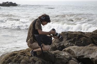 Chisa Hughes on rocks by ocean with camera