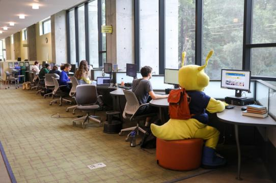 Sammy Slug and students sitting at computer stations with their backs turned to the camera